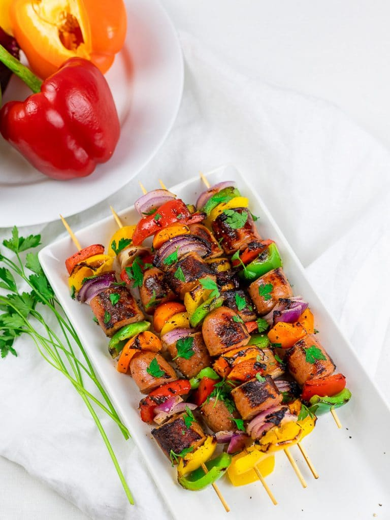 Grilled chicken sausage kabobs on a white plate with red and orange peppers