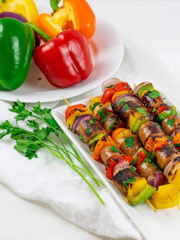 Grilled chicken sausage kabobs on a white plate with red and green peppers