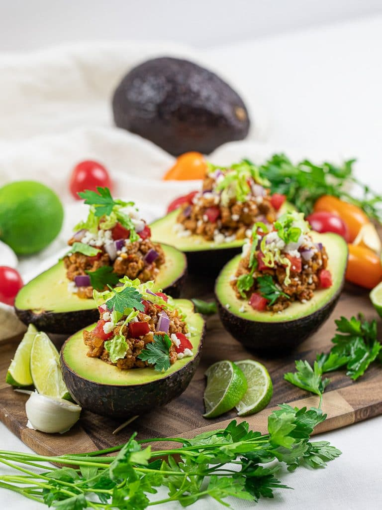 Keto taco stuffed avocado boats with lime, taco meat, tomatoes, and cilantro on a wooden board