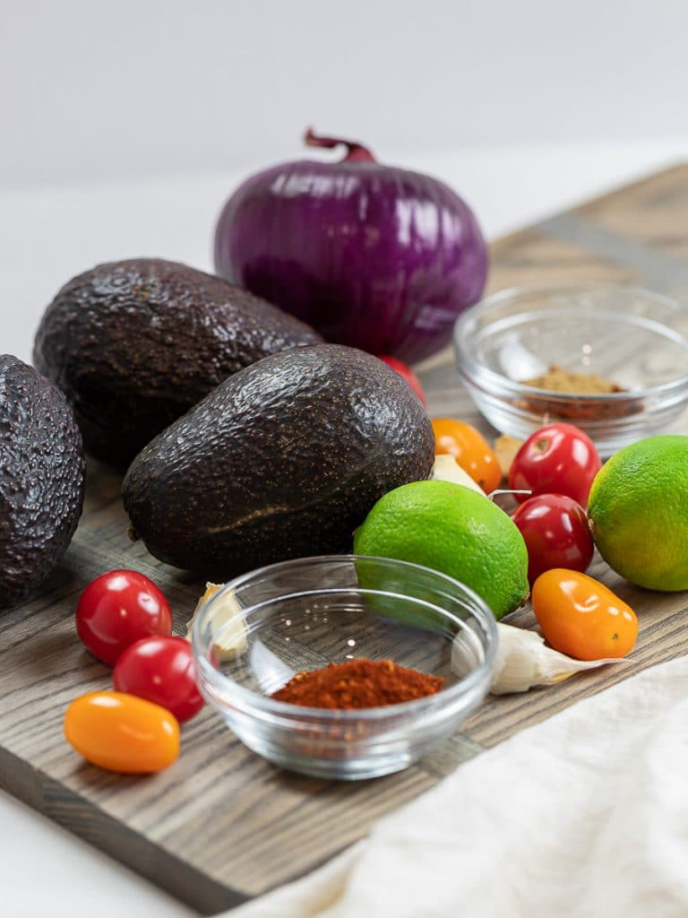 avocados, taco spices, tomatoes, lime, red onion on a wooden board