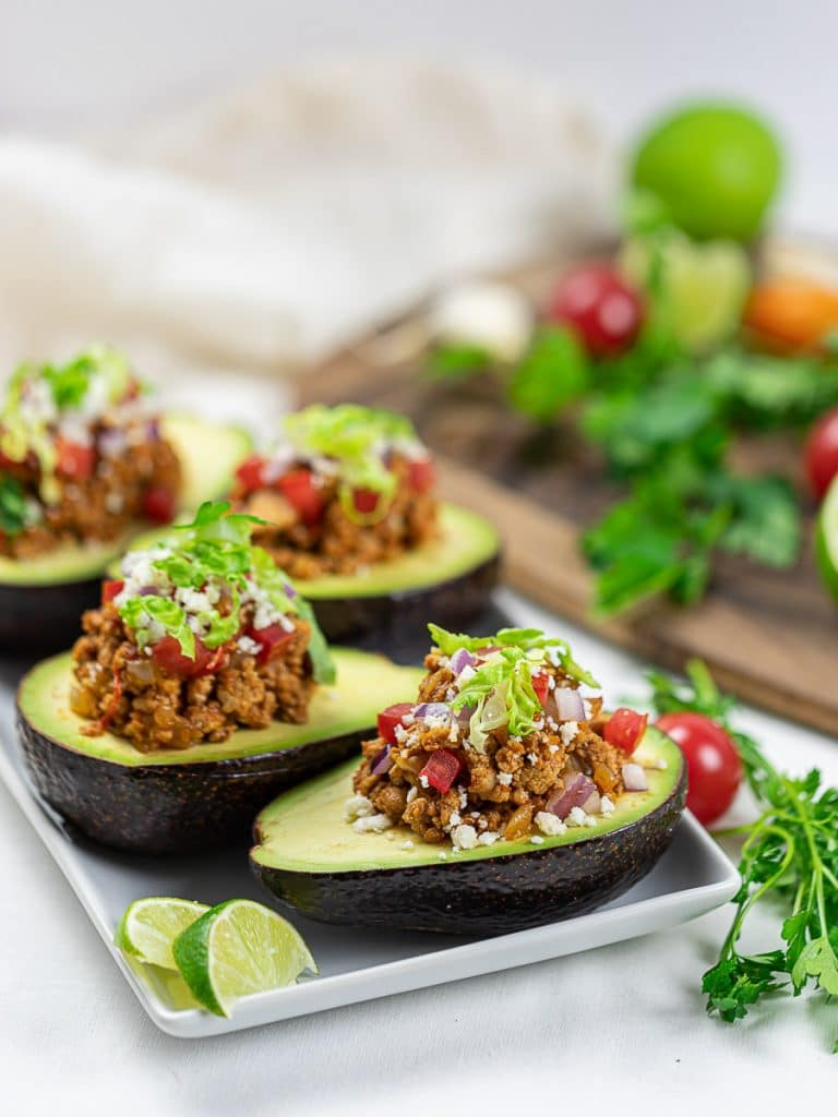 Keto Taco Stuffed Avocado Boats with lime, taco meat, tomatoes, and cilantro on a white plate