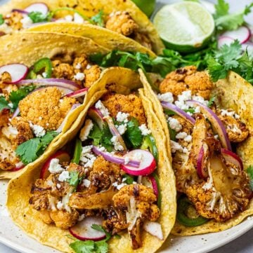 roasted chipotle cauliflower tacos with lime, radish, jalapenos in corn tortillas