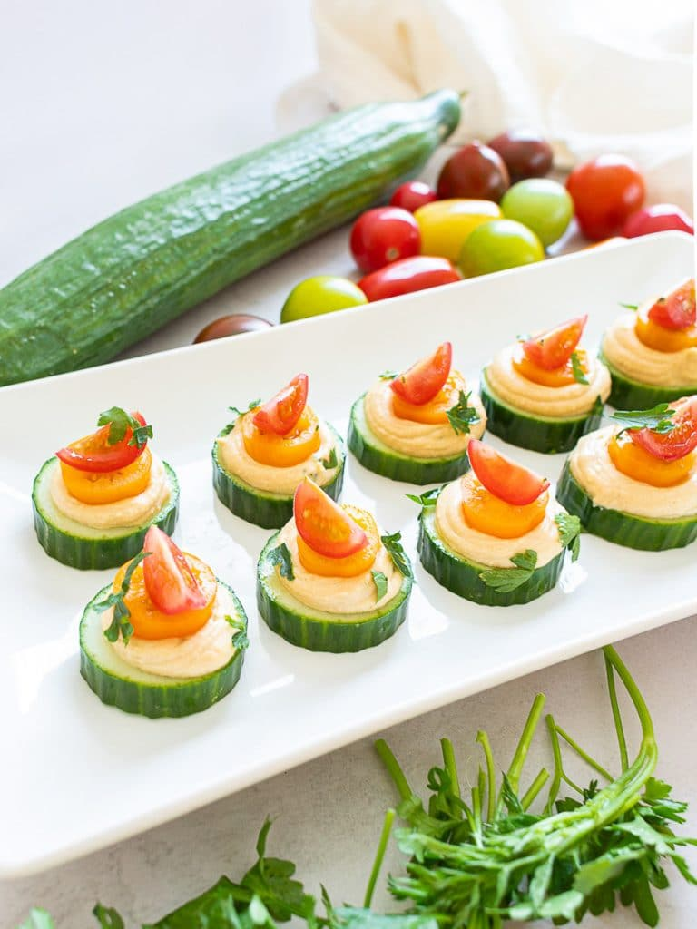 vegan cucumber hummus bites with red and orange cherry tomatoes on a white plate