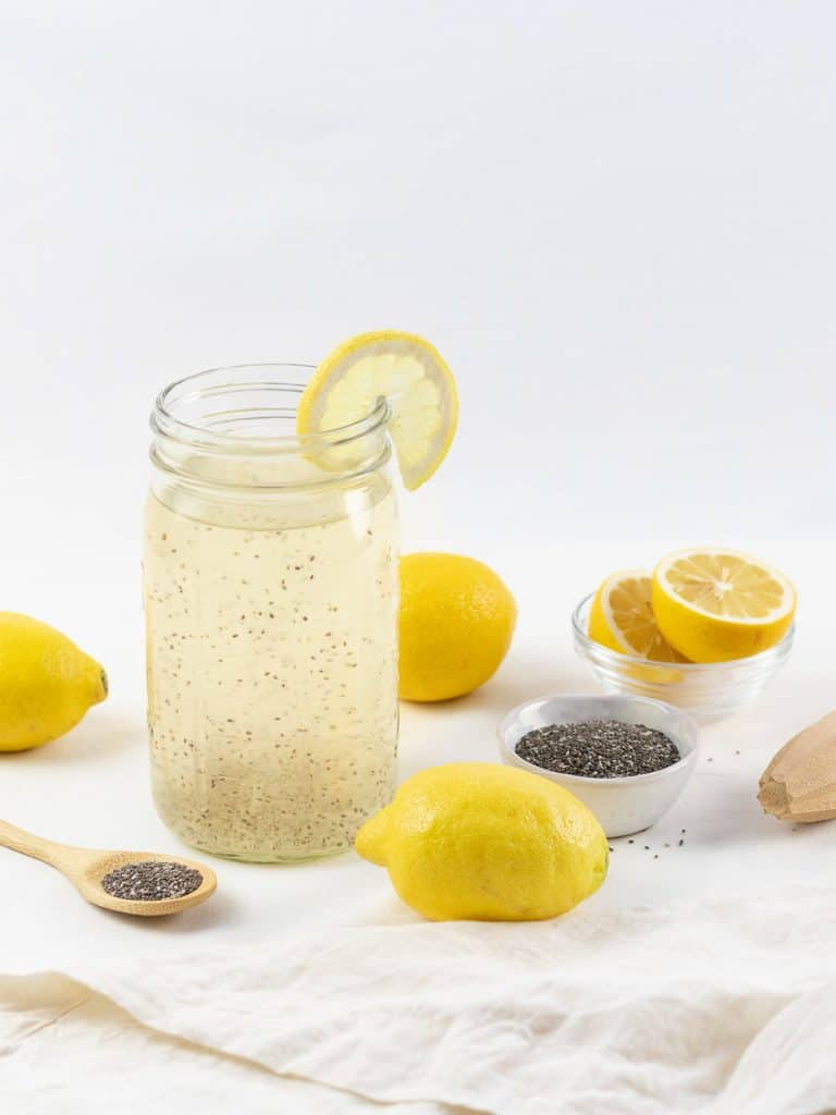 Chia fresca, chia lemonade in a mason jar next to lemons and chia seeds on a white surface