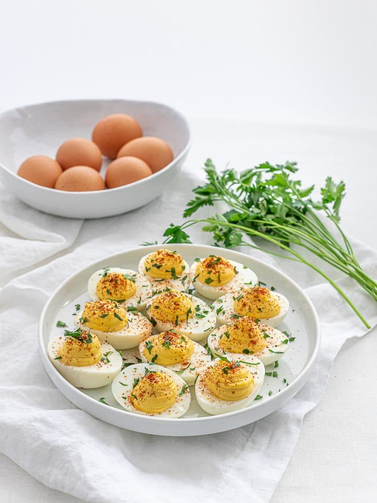 classic keto deviled eggs with parsley and paprika on a white plate