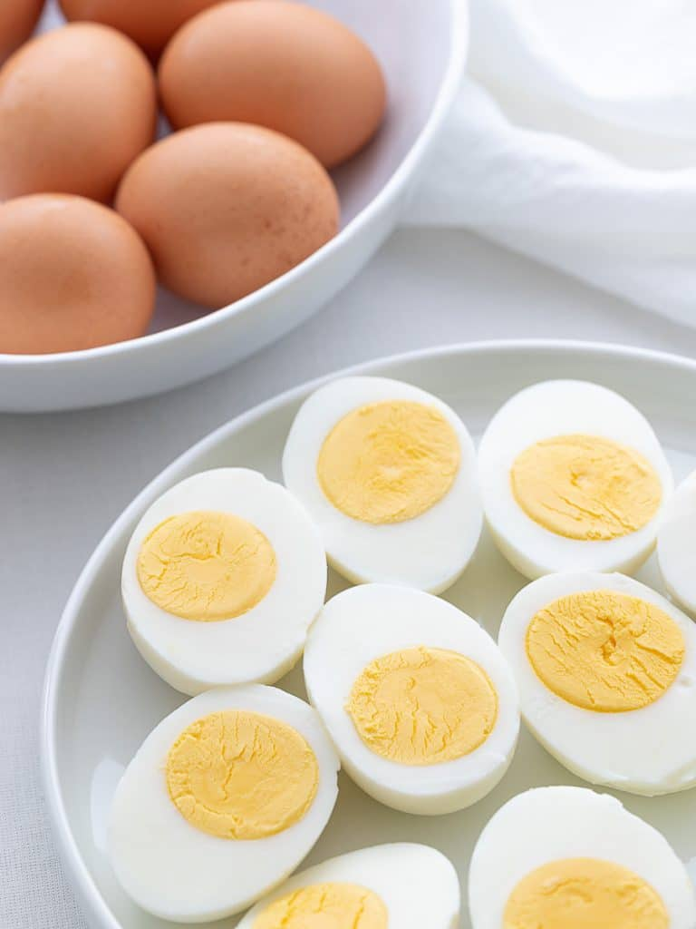 hard boiled eggs cut in half on a white plate next to brown eggs