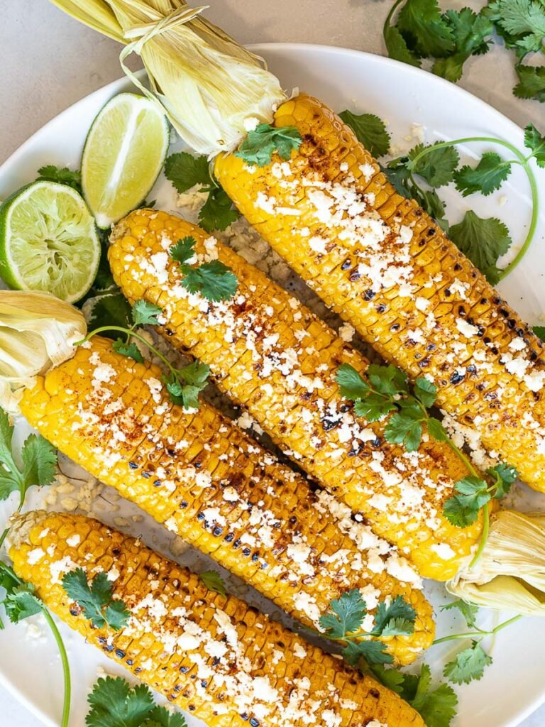 Healthy Grilled Mexican Street Corn on the cob (Elotes) with lime, cilantro, and cotija cheese on a white plate