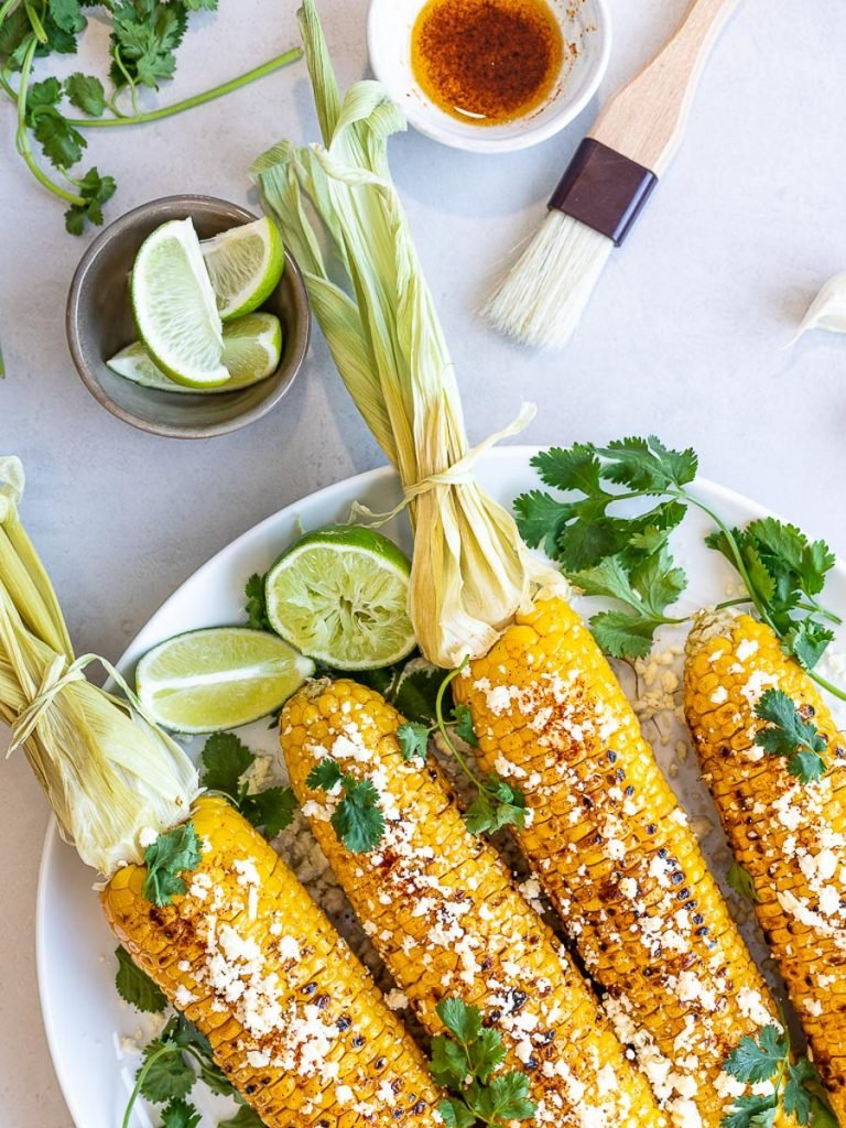 Healthy Grilled Mexican Street Corn (Elotes) with chili oil, lime, and cilantro on a white plate