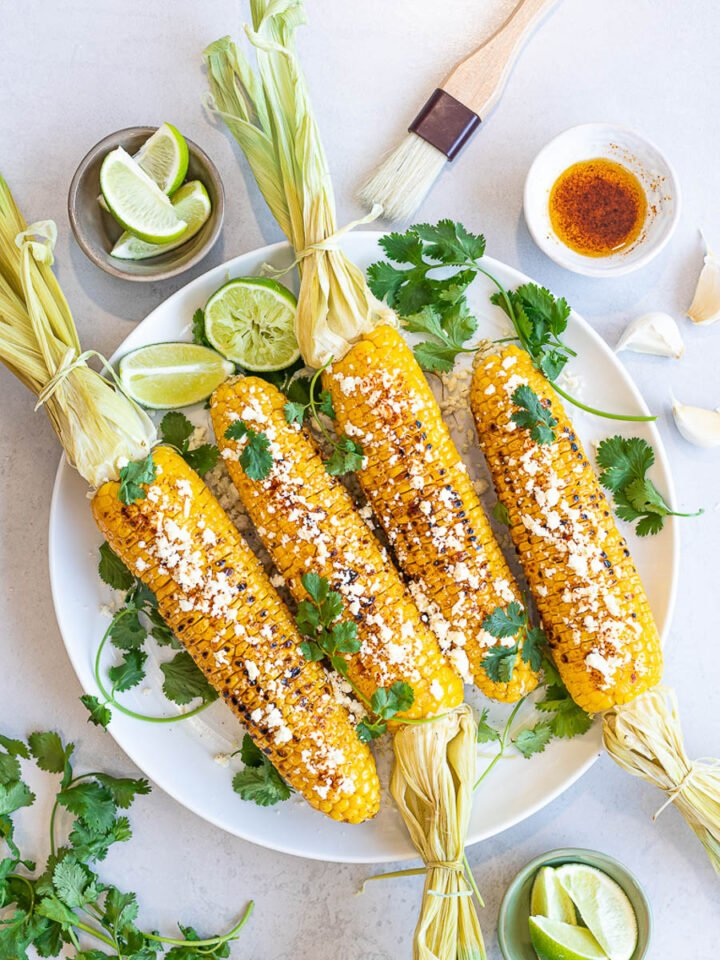 Healthy Grilled Mexican Street Corn (Elotes) with lime, cotija cheese, and cilantro on a white plate