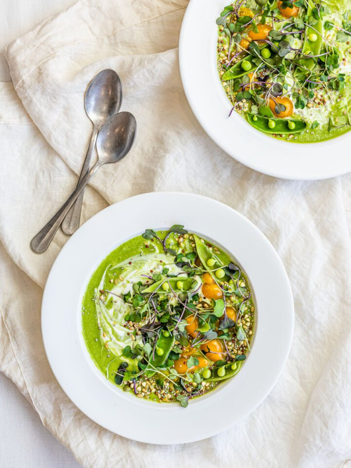 Two bowls of chilled vegan cucumber avocado soup with peas, tomatoes, and microgreens in white bowls.