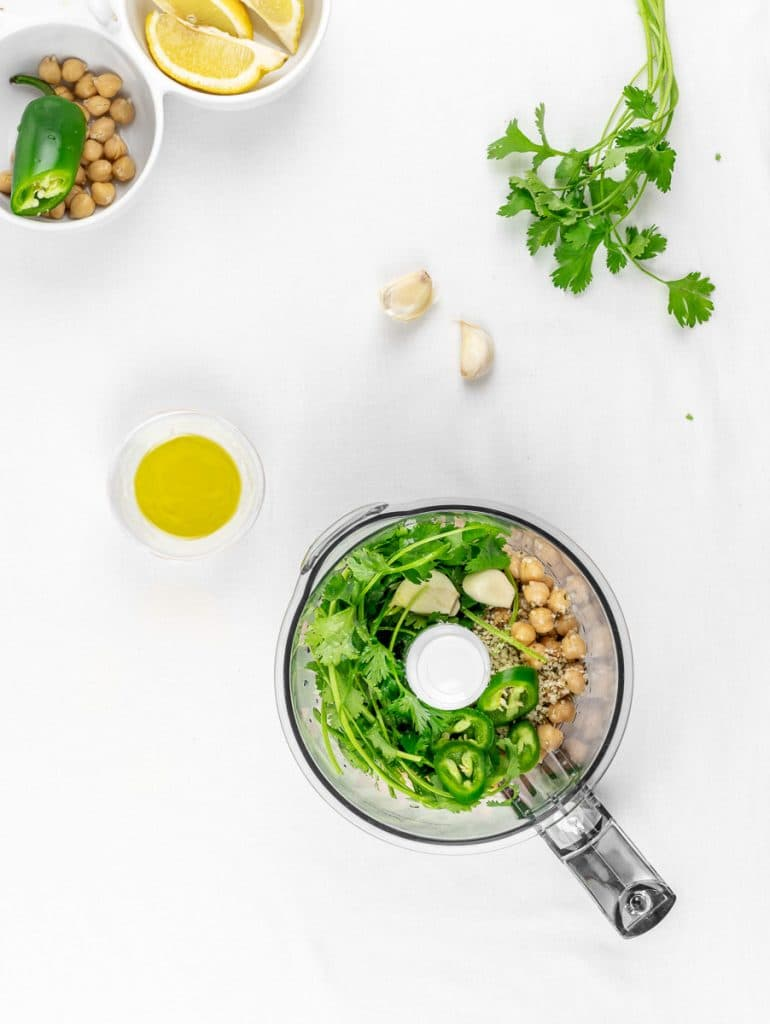 ingredients for cilantro jalapeno hemp seed hummus in a food processor with garlic and lemons