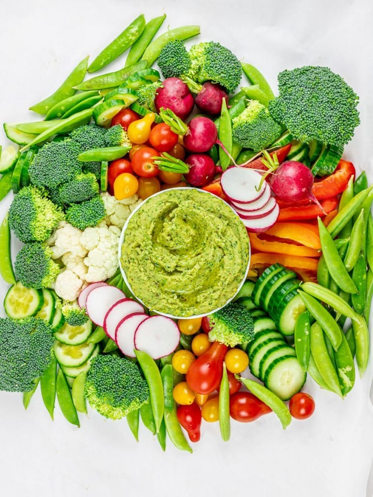 cilantro jalapeno hemp seed hummus surrounded by a vegetable platter