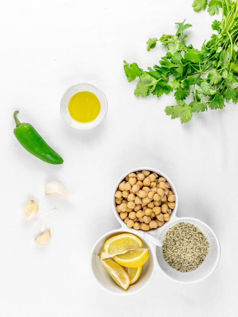ingredients for cilantro jalapeno hemp seed hummus in a bowl with garlic and lemons