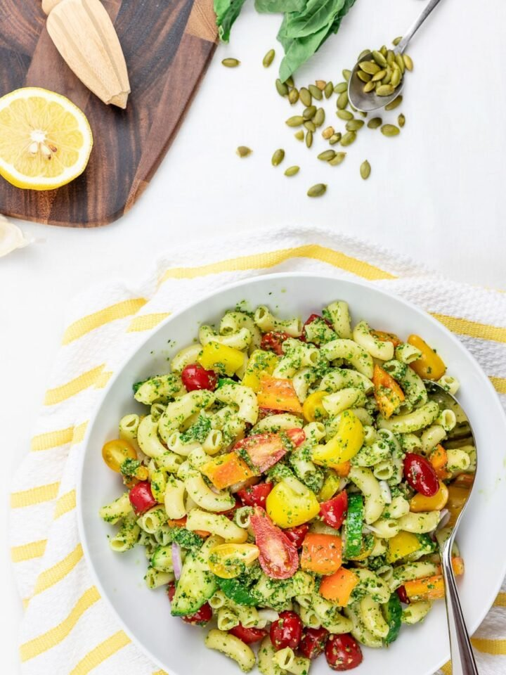 cold vegan pesto pasta salad with tomatoes and vegetables in a white bowl with lemon