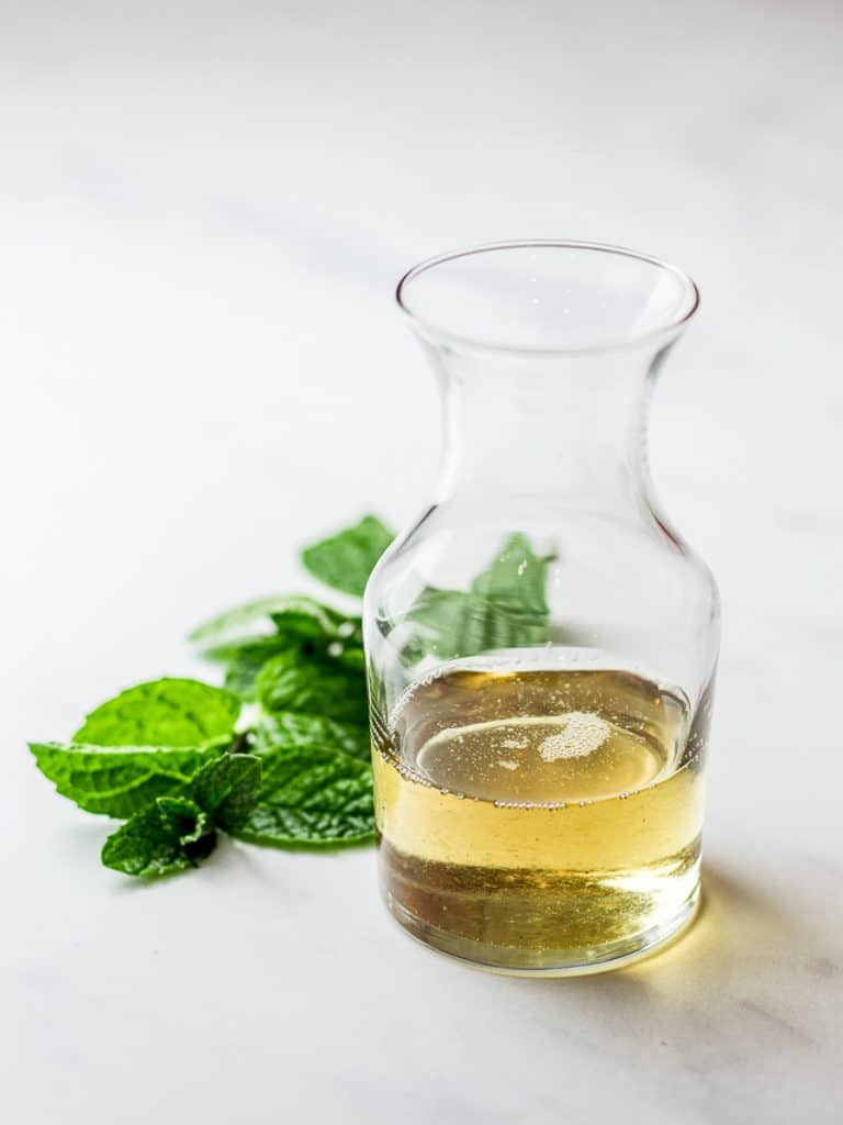 mint simple syrup in a glass jar with mint leaves