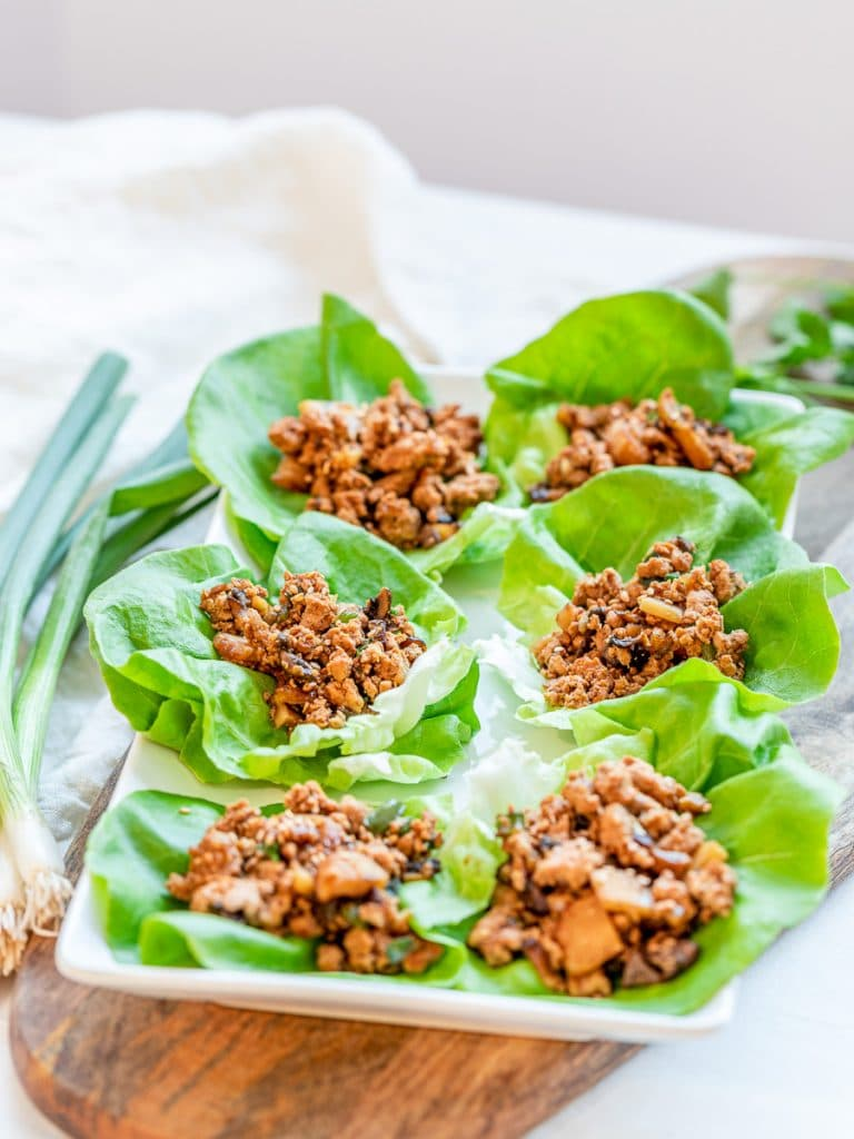PF Chang's inspired chicken lettuce wraps on a wooden board with scallions