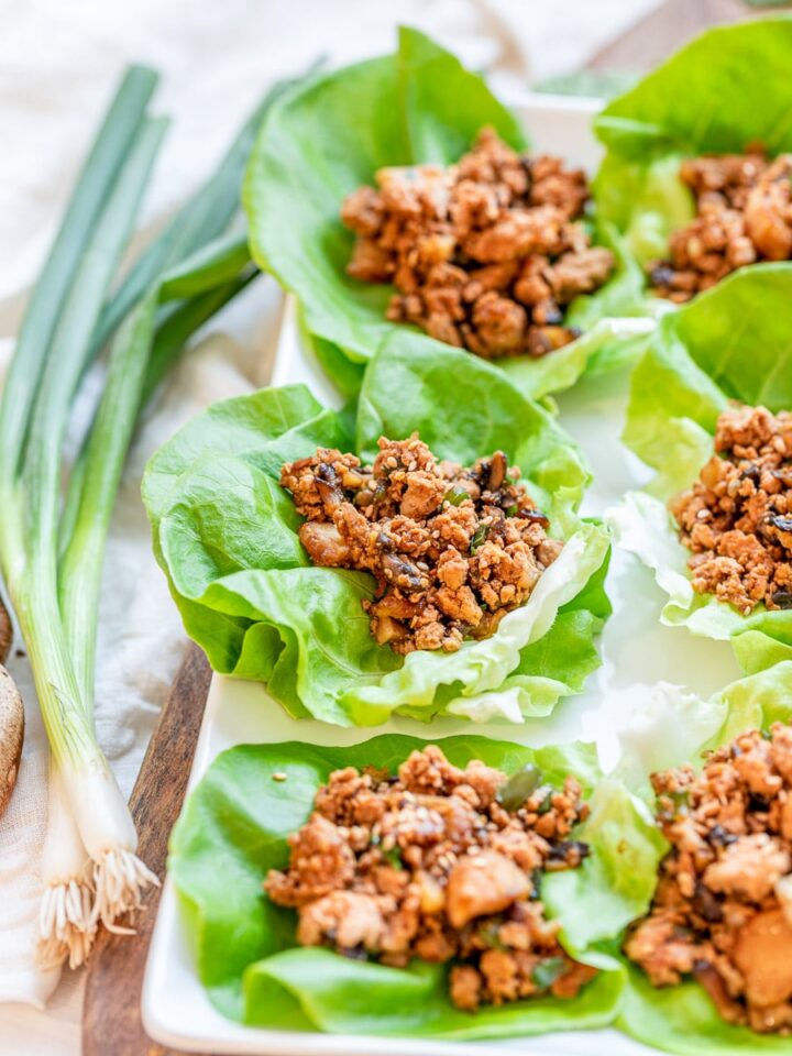 PF Chang's inspired chicken lettuce wraps on a wooden board with scallion