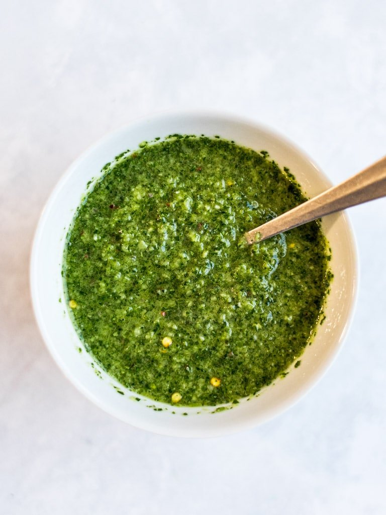 Asian chimichurri sauce in a bowl with a silver spoon with white background