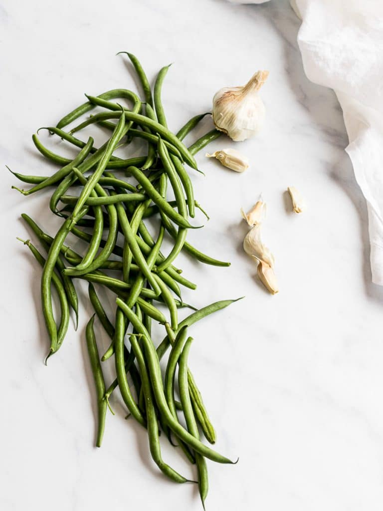 green beans with garlic on a white background