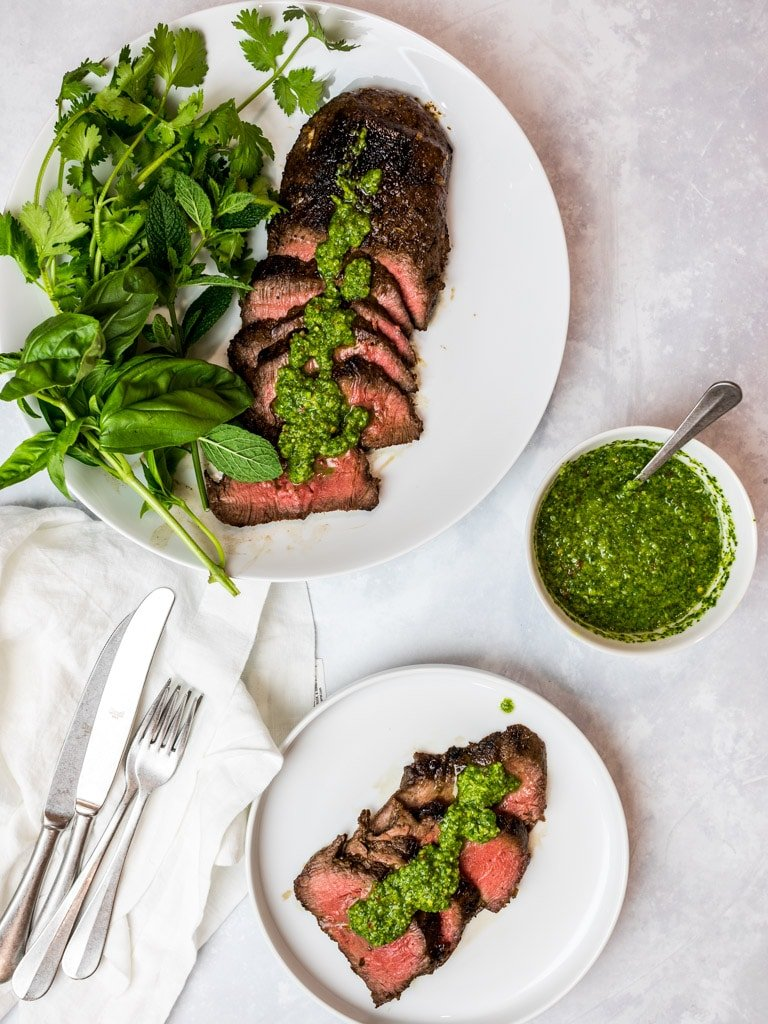 Asian marinated flank steak, spicy Asian chimichurri steak on white plates