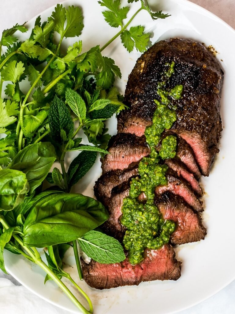 Asian marinated flank steak, spicy Asian chimichurri steak with fresh herbs on a white plate
