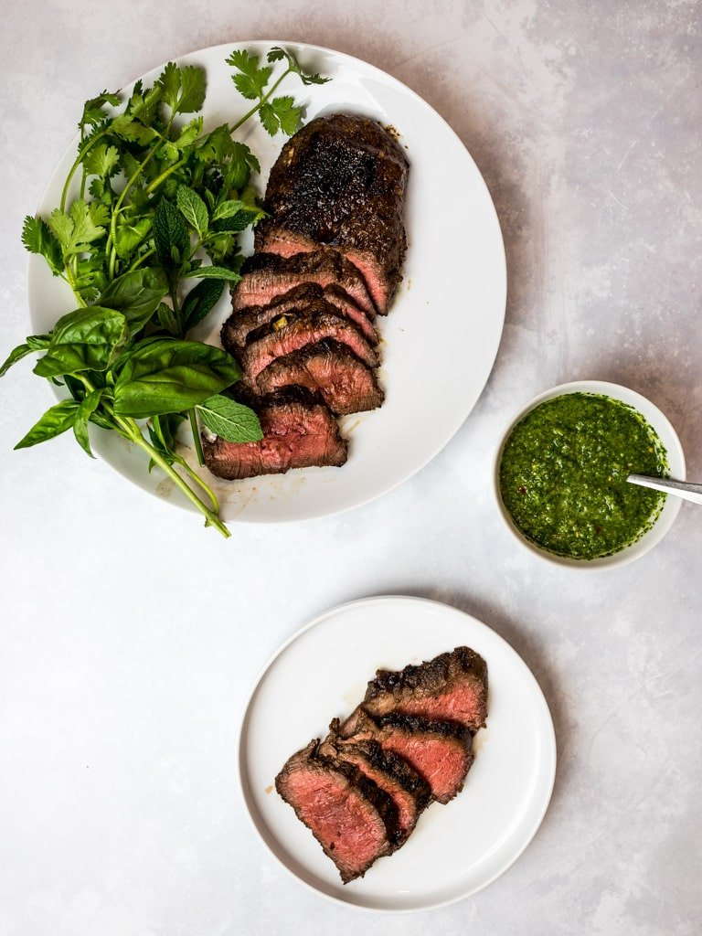 marinated Asian flank steak with spicy Asian chimichurri on white plates with herbs