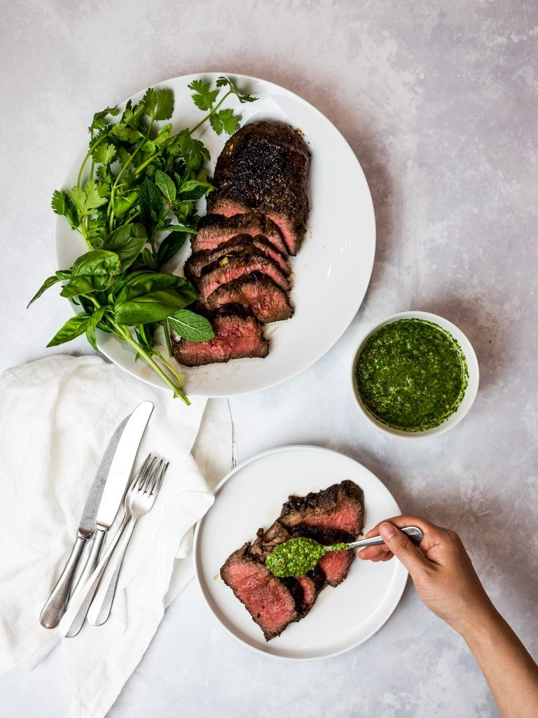 Asian marinated flank steak, spicy Asian chimichurri steak on white plates with herbs