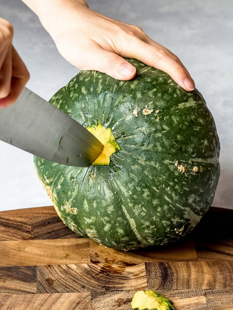 cutting a kabocha squash with a knife on a wooden cutting board