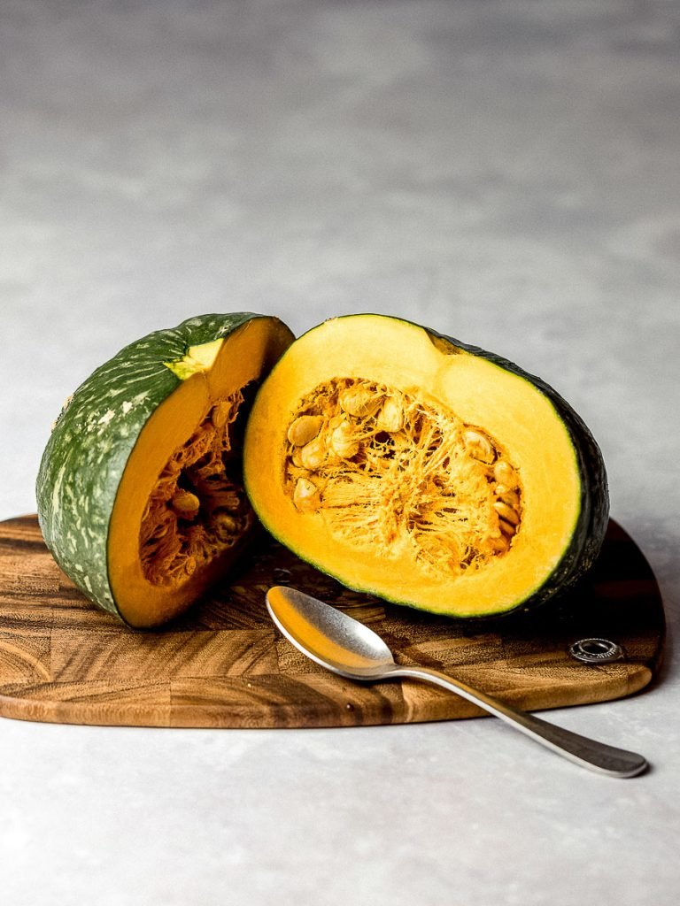 kabocha squash cut in half on a wooden cutting board with a silver spoon