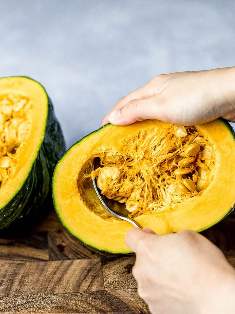 removing the seeds from a kabocha squash with a spoon