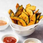 kabocha squash fries in a white bowl with ketchup and condiments