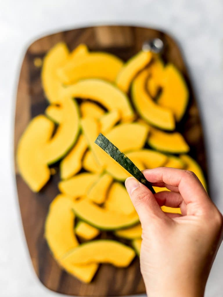 kabocha squash thinly sliced on a wooden board