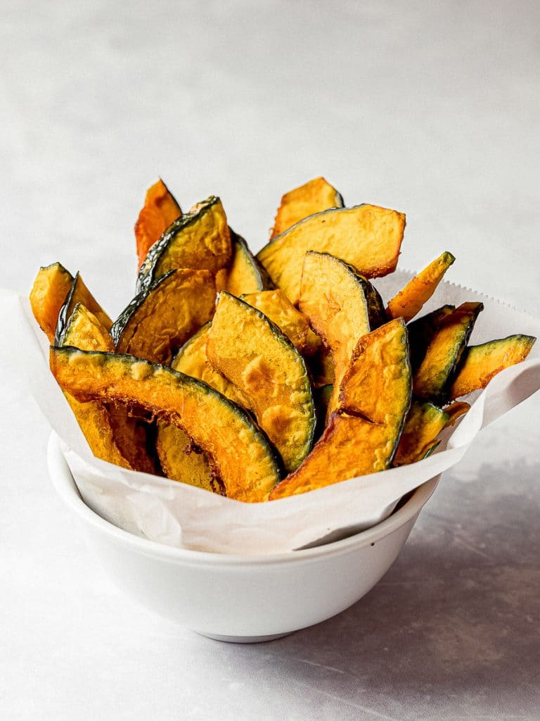 kabocha squash fries in a white bowl with parchement paper