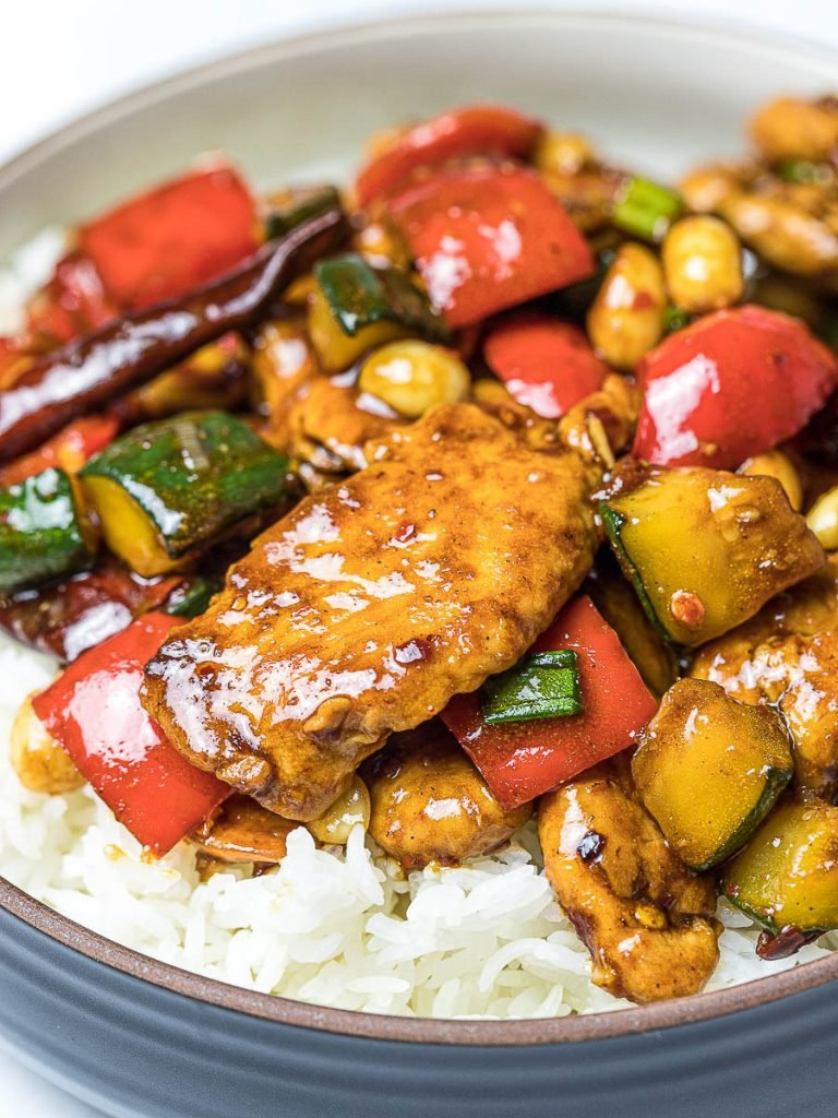 Panda Express Kung Pao Chicken Copycat on top of steamed rice in a dark bowl