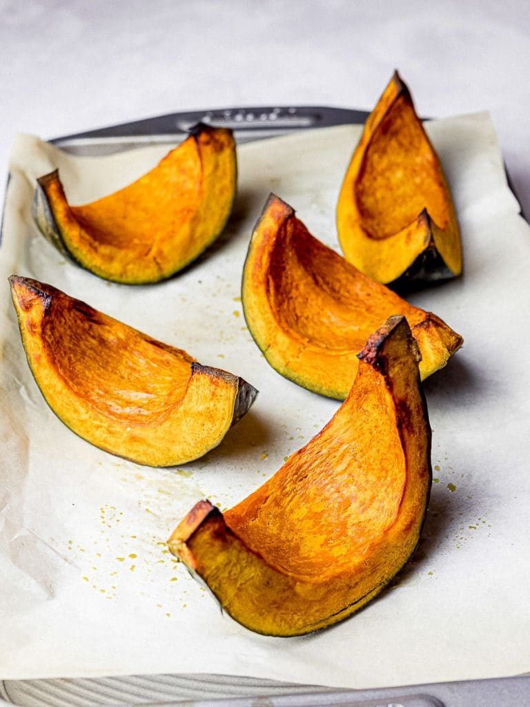 golden brown roasted kabocha squash wedges on a baking tray