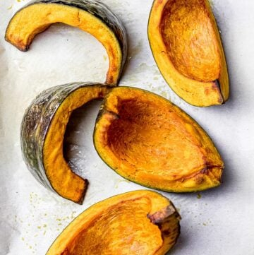 golden brown roasted kabocha squash wedges on parchment paper