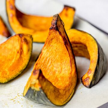 roasted kabocha squash wedges on parchment paper with baking tray