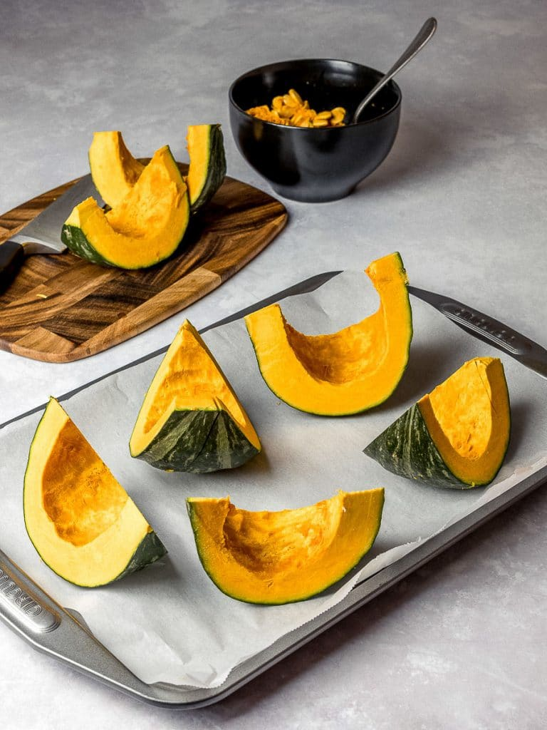 kabocha squash cut into wedges on a baking tray for roasting