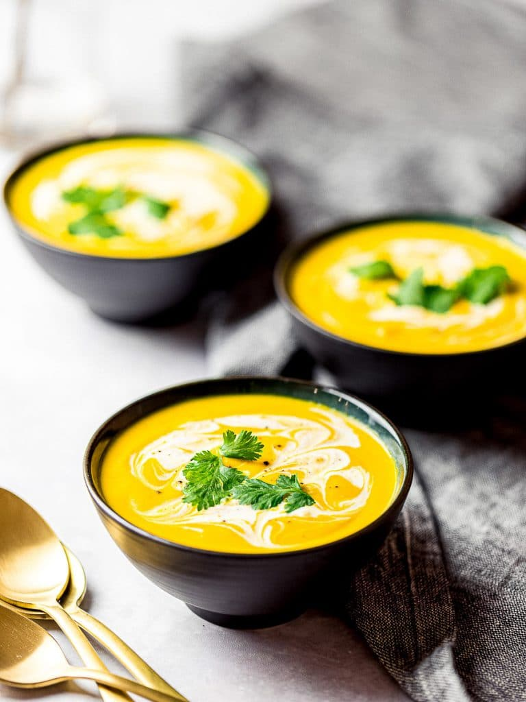 roasted kabocha squash soup, vegan pumpkin soup in black bowls garnished with cream and herbs
