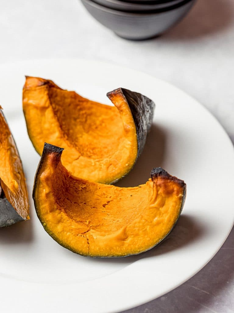 roasted kabocha squash wedges on a white plate