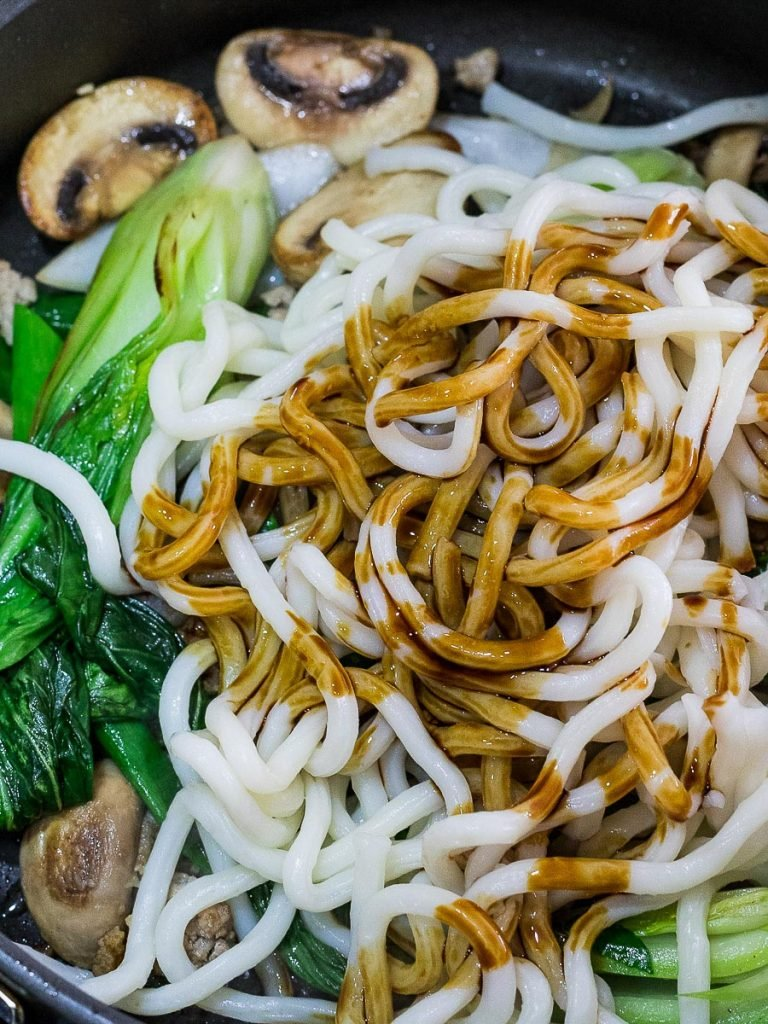 udon noodles stir fried with sauce, bok choy, and mushrooms