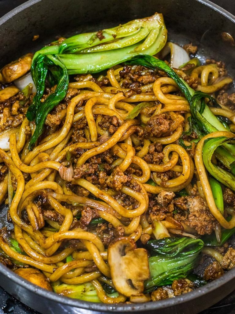 yaki udon, stir fried udon noodles with mushrooms and bok choy in a pan