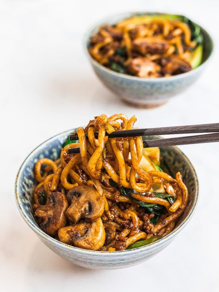 yaki udon, stir fried udon noodles with mushrooms and bok choy in a blue bowl