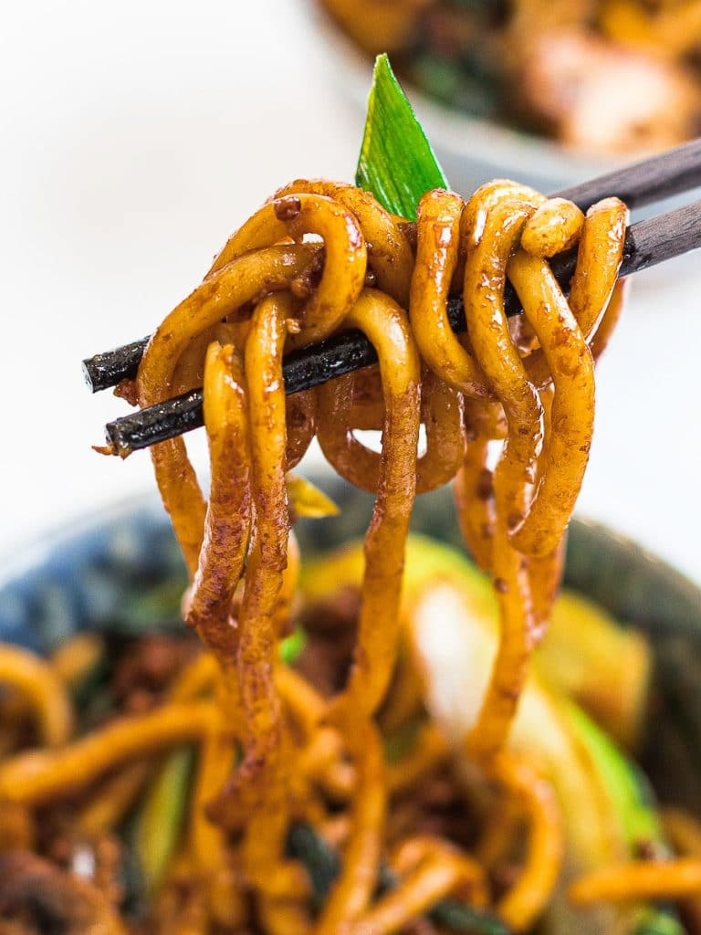 yaki udon, stir fried udon noodles held by chopsticks