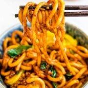 a bowl of yaki udon, stir fried udon noodles held by chopsticks