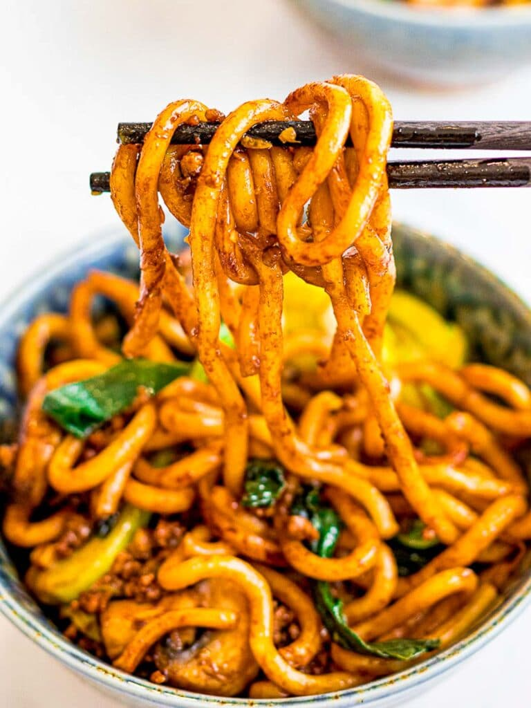 a bowl of yaki udon, stir fried udon noodles held by chopsticks