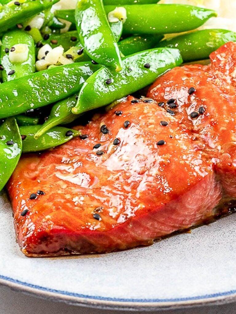 easy marinated and baked teriyaki salmon with sugar snap peas on a blue plate