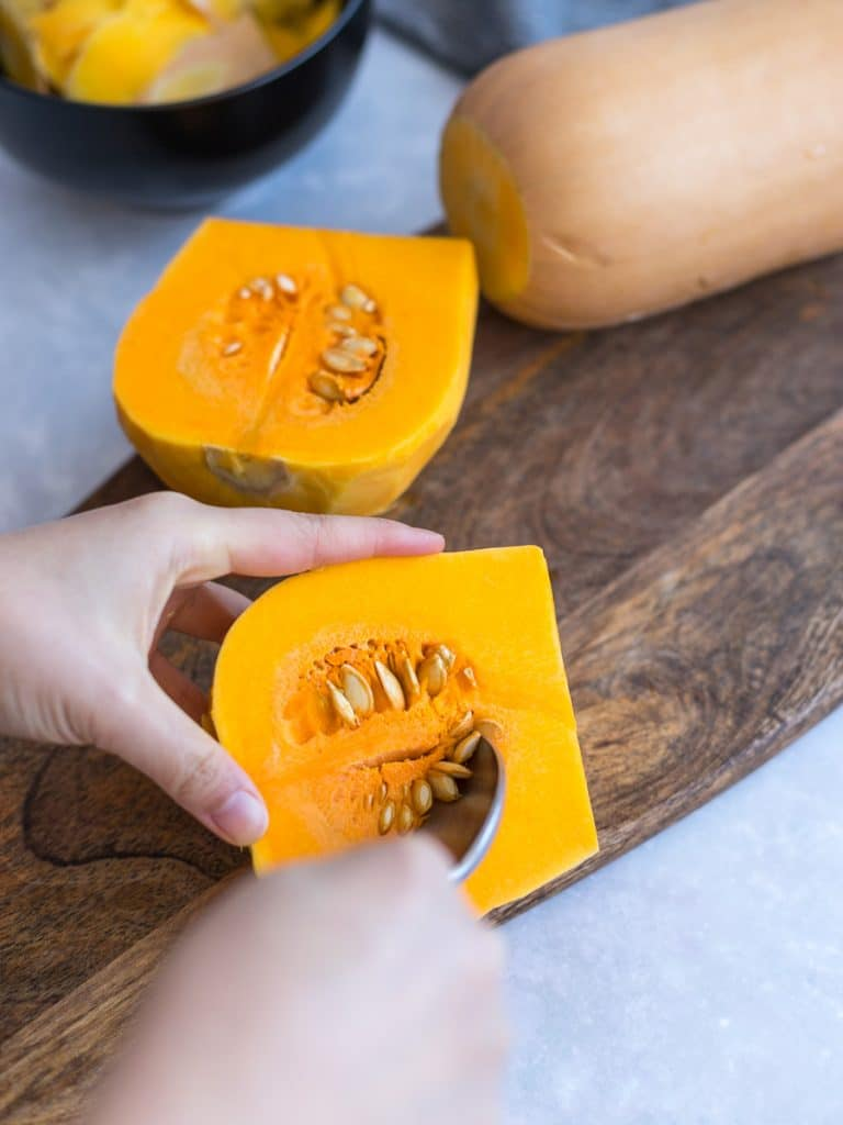 scooping the seeds out of a butternut squash with a spoon