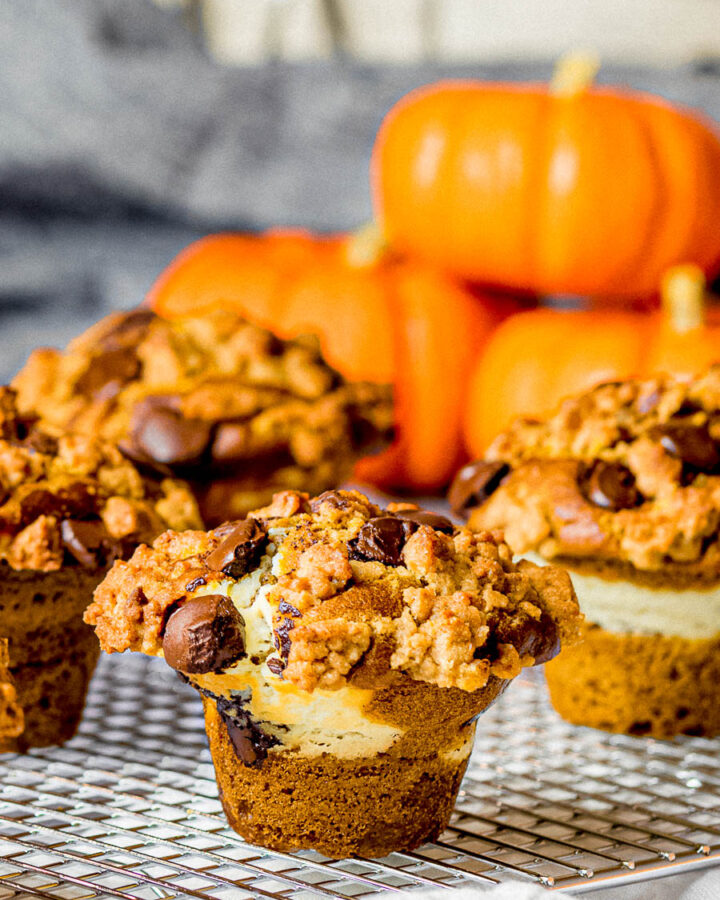pumpkin chocolate chip muffins with cream cheese filling and streusel topping on a cooking rack