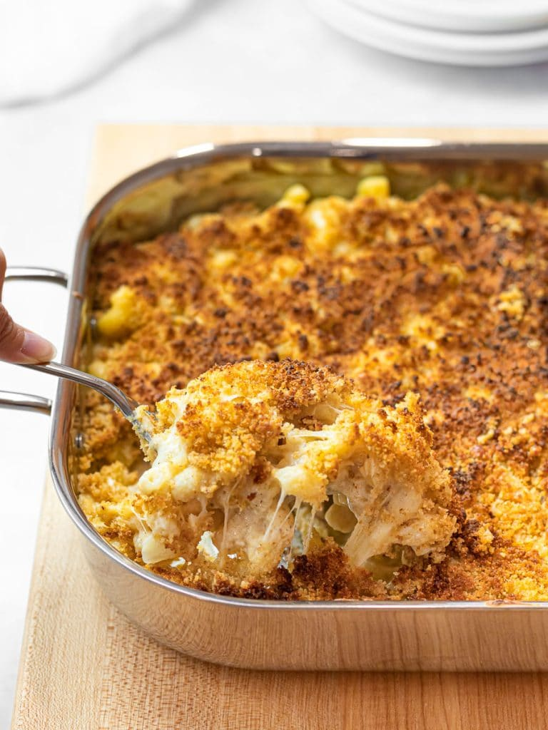 spoonful of baked gruyere mac and cheese with a golden brown breadcrumb topping
